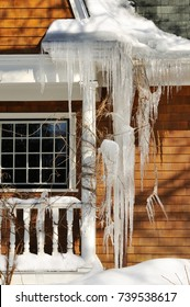 Huge icicles hanging from gutter and covering house window. Winter scene
