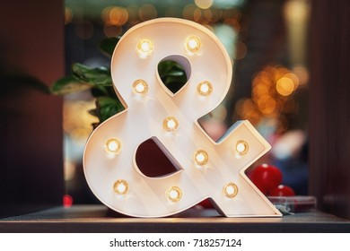 A huge illuminated ampersand on the table