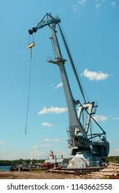 Huge industrial cargo crane at a port over blue sky background