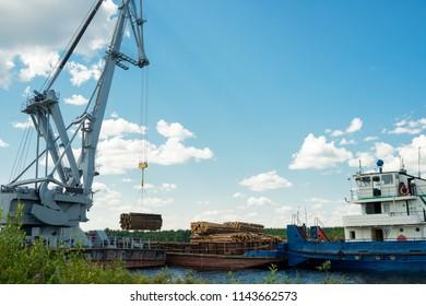 Huge industrial cargo crane at port loads timber on barge for transportation
