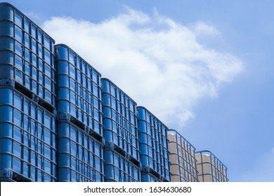 Huge industrial IBC outdoor storage with blue sky above.