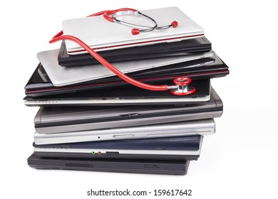Huge laptop pile with a red stethoscope isolated on white
