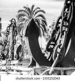 huge Large old ship anchor as a park decoration with a large fountain, iron scrap from an old ship, use as a fountain decoration, Spanish design, an old screeching ship chain balck and white, water