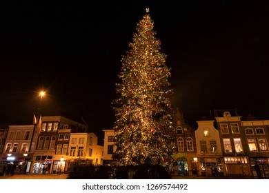 Huge lighted Christmas tree at night on the market of Gouda with a row of medieval houses with different facades. The Netherlands, Europe.