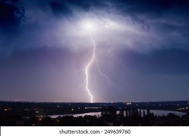 Huge lightning from dark stormy sky strikes small town