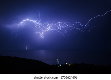 Huge lightning in the sky over the sea and the coast with a small village