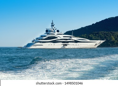 Huge luxury motor yacht cruising offshore in a calm ocean passing a forested coastline viewed over the wake of a passing ship