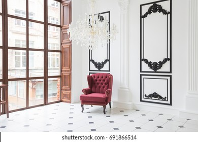 Huge luxury white hall with unique interior. Black and white tiles on the floor, white and black stucco on the walls, high fireplace with mirror mosaic, three-meter crystal chandelier and grand piano