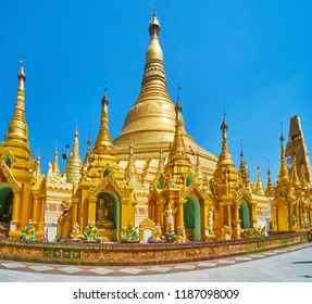 The huge main stupa of Shwedagon Zedi Daw is towering behind the hundreds of small outer stupas, decorated with ringing hti umbrellas and Buddha images, Yangon, Myanmar.