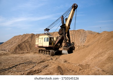 Huge mining excavator in the sand open-pit. Biggest digger working in quarry. Largest tracked machine with electric shovel. Heavy duty electric-powered mining equipment