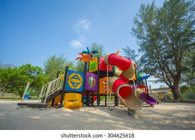Huge modern kids playground with ladders, slides and crawl constructions on sand in park
