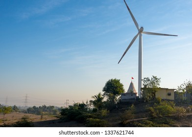 Huge modern windmill on hills with buildings in front and blue sky behind. These are part of massive wind farms generating clean green renewable energy for sustainability in India Rajasthan