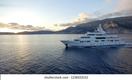 A huge motor yacht pick up small speed boat on the sunset