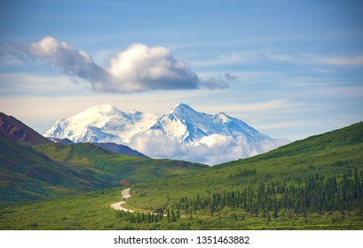 With its huge mountains and surrounded by a wonderful biodiversity lies the Denali National Park and Preserve. Touristic route and cloud sky. Landscape, fine art. Parks Hwy, Alaska, EUA: July 28, 2018