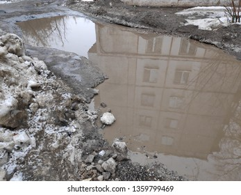 A huge muddy puddle of melting snow in the courtyard of a residential building. Sleeping area of the city, old houses, cheap housing. Poor utilities work. Lack of sidewalks.