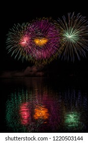 Huge multicolor stars in fireworks over surface of Brno's Dam with lake reflection