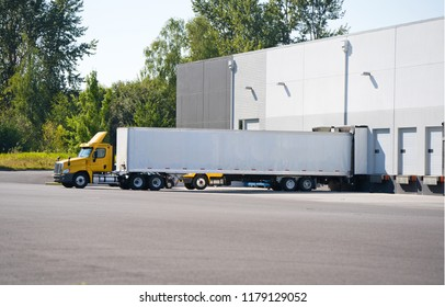 A huge number of big rig semi trucks are loaded and unloaded in the docks of huge warehouses, detaches semi trailers, attaching already loaded ones, and again the truckers kings of roads are set off