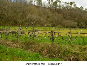 Huge number of old, hanging bicycles attached to wooden fence in rural landscape.