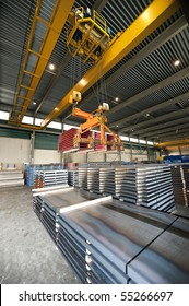 Huge overhead crane, handling pallets conaining steel sheet at a warehouse
