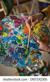 A huge palette in the hands of the artist at work.