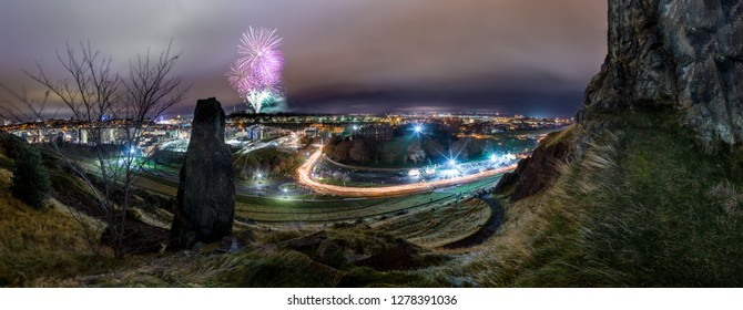 Huge Panorama of Edinburgh's Hogmanay Torchlight procession with fireworks in background above Calton Hill
