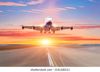 Huge passenger aircraft take off from runway airport in the evening at sunset, the sky and picturesque clouds