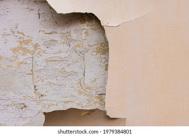 Huge patch paint  with coating is missing from a facade wall of the building. Cracks on the surface of the wall that needs repair.