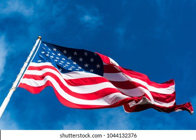 huge perfect American Flag waving in the breeze with the perfect blue sky background. A patriotic symbol of the United States of American one nation under god with liberty and justice for all