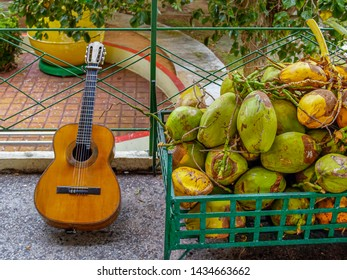 A huge pile of large yellow-green coconuts and an old worn acoustic guitar. The essential attributes of a tourist holiday in Cuba.