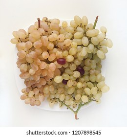 Huge pile of sultana green grapes on stylish square plate and white background. Flatlay closeup