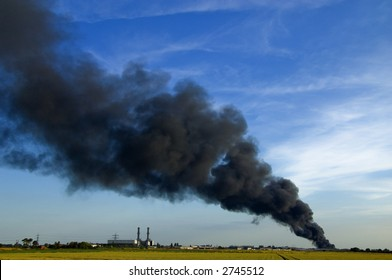 Huge plume of black smoke from fire rising high above flat land against blue sky
