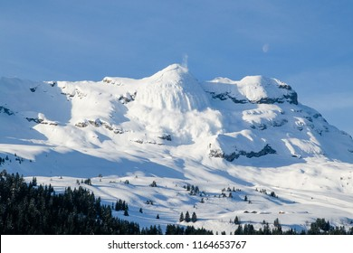 Huge real avalanche in the French Alps with the moon and blue sky