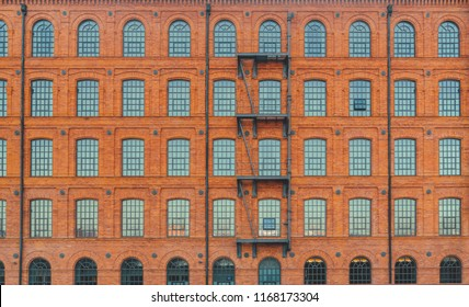 Huge red brick classic industrial building facade with multiple windows and fire escape ladder stairs. Industrial background. Loft inspiration. Construction facade concept. Vintage effect.