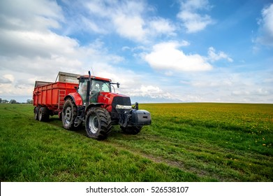 huge red tractor in floral spring  field under the blue cloudy sky
