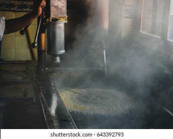 Huge ring of Churros boiling in oil, steam coming up. Inside old churreria. Spanish (Mexican) cuisine