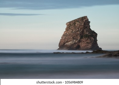 huge rock cliff isolated in ocean in long exposure in sunset sky, hendaye, basque country, france
