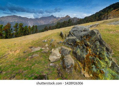 Huge rock on Bugyal, alpine pasture lands, or meadows, in higher elevation range of Himalayas in Uttarakhand, called nature's own gardens. View of Himalayas on Trekking route to Tunganath.