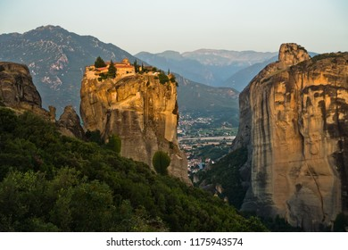 Huge rocks with christian orthodox monasteries at sunrise with Meteora valley in background near Kalambaka, Thessaly, Greece
