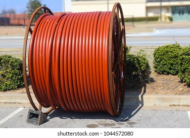 Huge roll of orange cable for underground cable installation sitting along a street