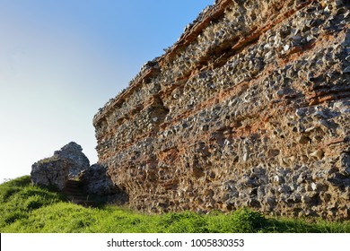 Huge Roman fortress walls built around 300AD at Burgh Castle to defend Norfolk, England, from raids by Saxon forces.