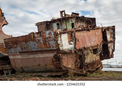 Huge rusty pieces of decommissioned marine ship that was cut and left on the shore.