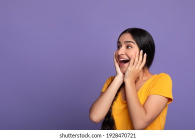 Huge Sale Or Promo Concept. Amazed indian woman screaming and touching her face in disbelief, looking at free copy space on purple studio background. Astonished young lady with open mouth