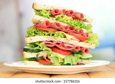 Huge sandwich on wooden table, on bright background