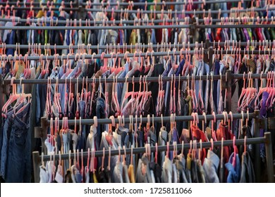 Huge selection of different used clothes for men, women and children on the rack in a second hand shop or thrift store. Concept of waste problem in fashion industry.