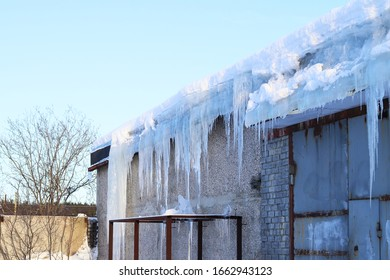 Huge sharp icicles hanging from the snowy roof of a brick building . Spring drops. Selective focus. Melting ice in the spring