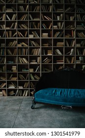 A huge shelving for books and elegant vitage blue sofa. Luxury and chic interior. daylight from window. stylish loft interior