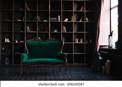 A huge shelving for books and a refined emerald sofa. Discreet and chic interior. daylight from window. Dark natural wood on the floor