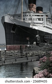 """Huge ship at dock with smoke coming out of top.  This photo has a """"vintage"""" look with a slight texture (grain) effect."""