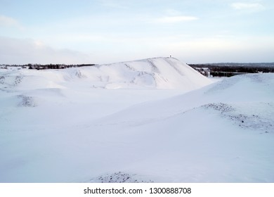 The huge slag heaps in Roros (Røros). A remnant of the massive copper mining industry that was located there. Picture taken in January 2019. A person can be seen on top of the heap as a reference.