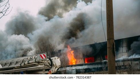 Huge smoke and fire flooding the sky, burning industrial warehouse or rubber factory in Voronezh, Russia
